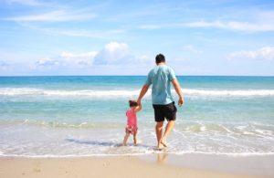 Padre con niña en la orilla de la playa