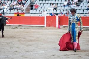 torero con capote rojo y toro más atrás en plaza de toros