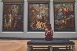 Mujer sentada en un banco frente a tres cuadros
